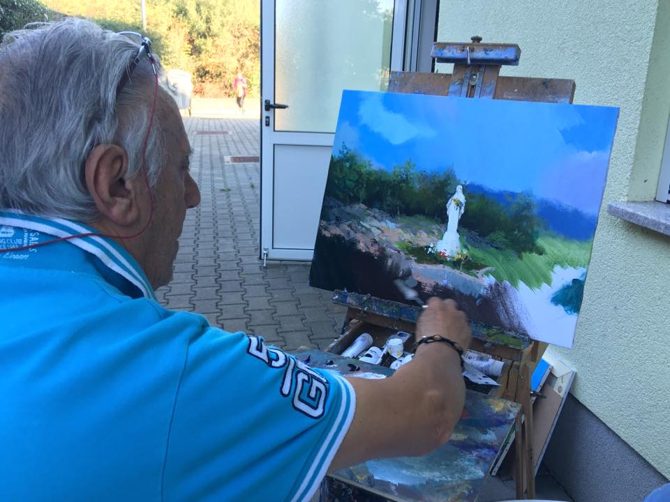 Italian artist Gianfranco Vianello paints a scene from the Apparition Hill movie in Medjugorje.